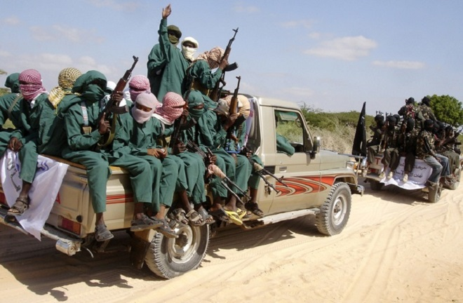 Militants of al Shabaab ride on pick-up trucks after displaying their weapons on the outskirts of Mogadishu, December 8, 2008. The hardline Islamist insurgent group al Shabaab has taken control of a central Somali trading town after fighting that killed at least 13 people and wounded dozens of others, residents said. REUTERS/Feisal Omar (SOMALIA)